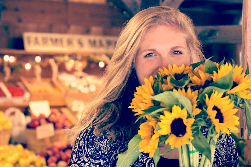 woman with a bouquet of supermarket sunflowers